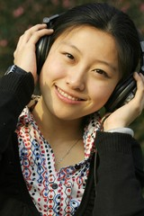 Portrait of an Asian businesswoman listening music