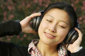Portrait of an Asian businesswoman listening music