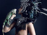 Young pagan priest in ritual suit with green iguana in his hands poster