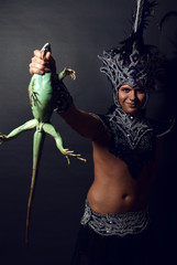 Young pagan priest in ritual suit with green iguana in his hands