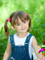 Little girl in jeans with blue eyes outdoor