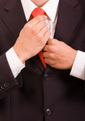 Detail of young businessman correcting a tie