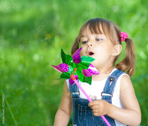 Little girl in jeans blowing on color propeller outdoor