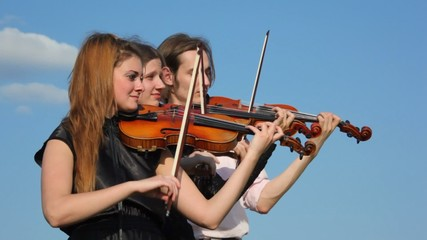 three musicians plays violin outdoors