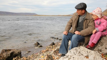 daddy with daughter sit on stone on riverbank
