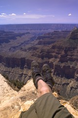 Man Sitting On Edge Of Canyon