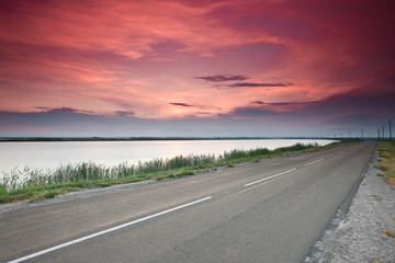 road under dramatic red sunset sky