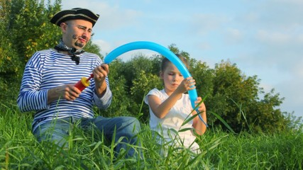 girl and man in pirate costume fills with gas balloon