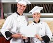 chefs holding white board in kitchen