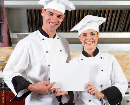 chefs holding white board in kitchen