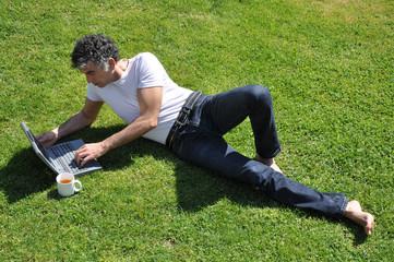 uomo col computer  nel parco