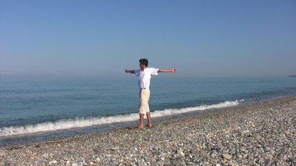 man warming up on beach against sea