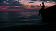 silhouette of teenager sits against sunset sky and throws stones