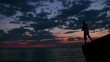 man stands on rock and throws pebbles into sea under sunset sky