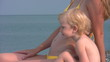 mother and little daughter sits on beach