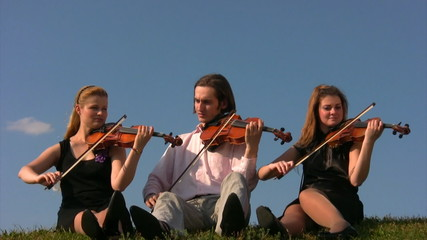 three musicians sits on hill and plays violins