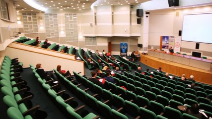 presentation hall with rows of seats, listeners and speaker
