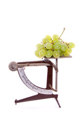 an antiqueted scale with white grapes on top isolate dover white