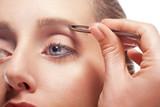 Woman plucking eyebrow poster