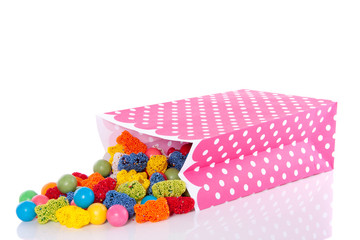 a pink dotted candy bag with mixed tasty sweets isolated over wh