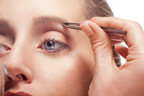 Woman plucking eyebrow