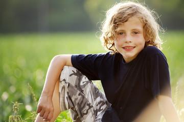 junge sitzt auf dem Rasen 2