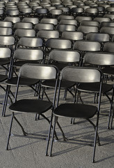 Empty rows of black plastic chairs