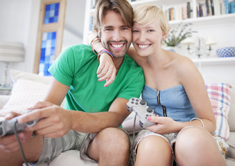 Couple hugging on sofa and playing video game
