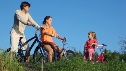 family with bicycles talks in summer park