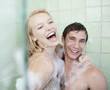 Couple in bathtub covered with soap suds