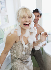 Couple covered with soap suds in bathroom