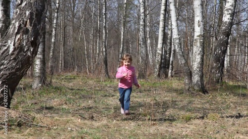 girl runs to camera in spring forest