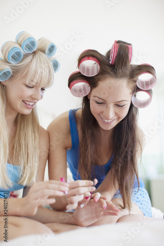 Women painting fingernails with curlers in hair