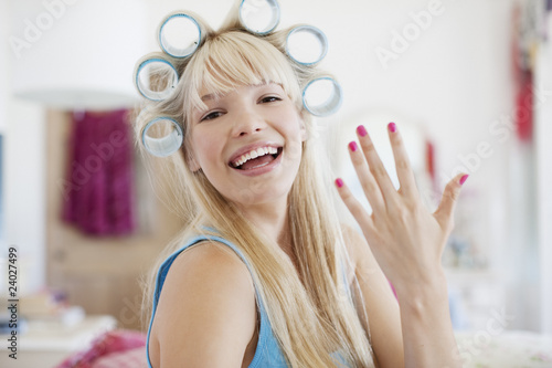 Woman with curlers in hair showing freshly painted fingernails