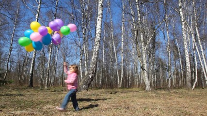 girl with bunch of balloons walks in forest