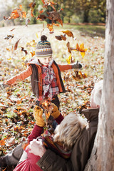 Playful boy throwing autumn leaves at grandparents