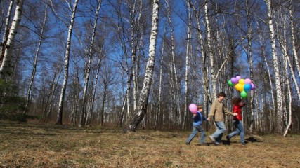 family with balloons runs in forest