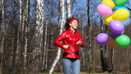 woman holds bunch of balloons and runs