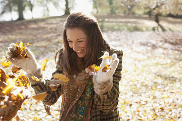 Laughing woman throwing autumn leaves