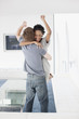 Couple hugging with arms raised in living room