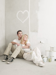 Couple sitting and relaxing under heart painted on wall