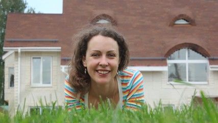 A smiling beautiful woman lays on grass near house