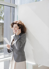 Businesswoman talking on cell phone by window