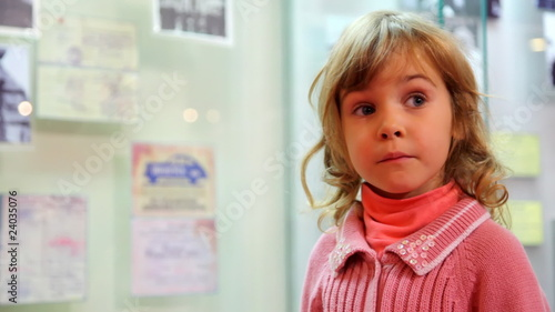 little girl  talking in front of bulletin board
