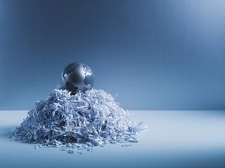 Metal globe on pile of shredded paper