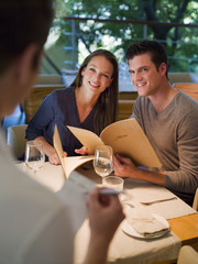 Waiter taking order from couple with menus at restaurant table
