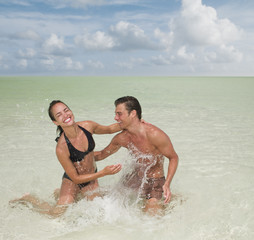 Couple splashing in ocean