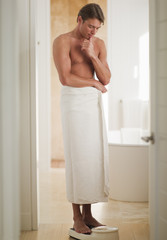 Man wrapped in a towel standing on bathroom scale