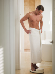 Man wrapped in a towel standing on bathroom scale with hands on hips