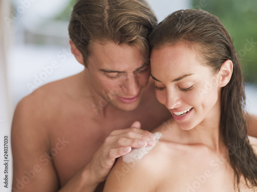 Man applying lotion to woman?s shoulder